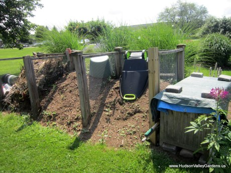 three garden compost bins, plant pots and tool  box in a garden