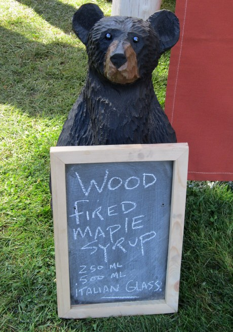 A wooden bear sculpture with a chalk-board sign for maple syrup