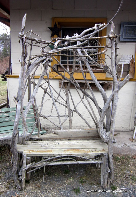 Garden chair made from reclaimed wood with a back of interwoven branches and sticks.