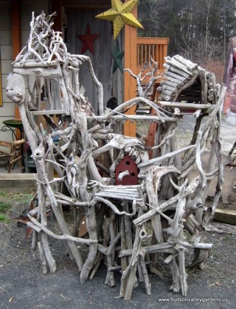 A sculpture designed for wild birds, includes a reclaimed bird house