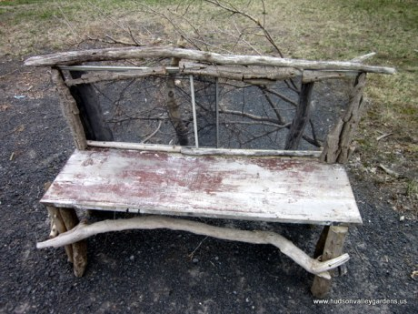A piece of hand-made outdoor furniture made from up-cycled wood and a mesh window screen.
