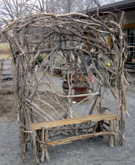 Large garden chair with a high back made from branches, the seat is made from re-purposed wood