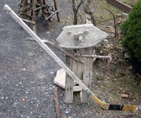 A small, humorous sculpture of a child ice hockey player made from reclaimed wood, the figure is holding a real hockey stick.