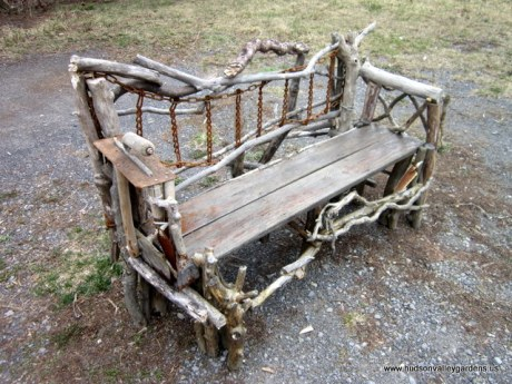 garden seat made from recycled wood, rusty chain with tools such as trowels incorporated into the design