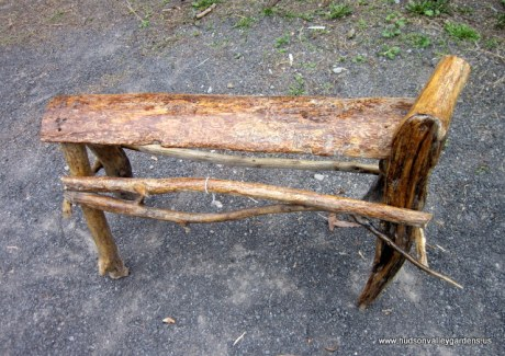 small wooden, decorative bench, constructed from reclaimed wood which has been varnished.