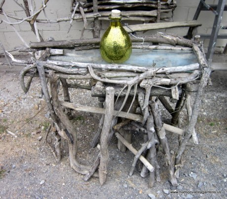 Country-style table made from up-cycled items. The top is a piece of discarded glass, the frame and legs are constructed from driftwood.